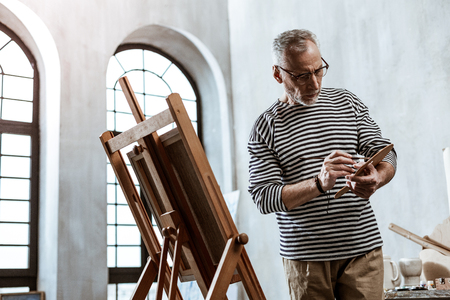 Busy artist. Professional experienced artist wearing striped shirt feeling busy while painting still life Imagens - 121927774