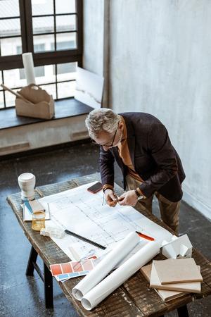 Making some notes. Grey-haired interior designer making some notes on the sketches in his light workshop Reklamní fotografie