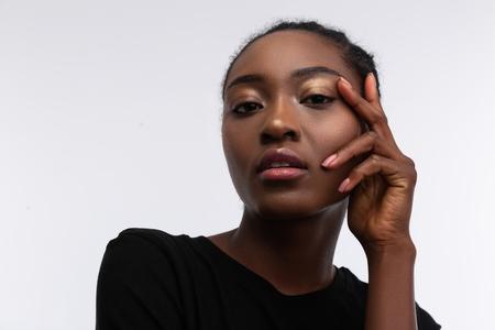 Nice natural makeup. Appealing young African-American woman with nice natural makeup touching her face