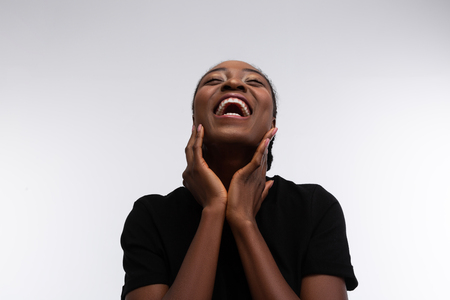 Woman laughing. Beaming African-American woman laughing out loud while feeling cheerful