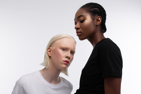 Non-racism organization. Serious professional models wearing white and black t-shirts posing for non-racism organization
