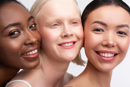 Lächelndes glückliches Gefühl. Drei ansprechende junge Frauen mit unterschiedlichem Teint, die sich glücklich lächeln