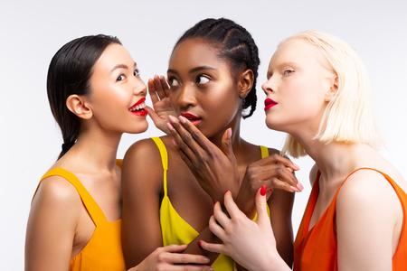 Frauen klatschen. Lustige gutaussehende Frauen mit unterschiedlicher Haut, die über ihr Leben klatschen Standard-Bild