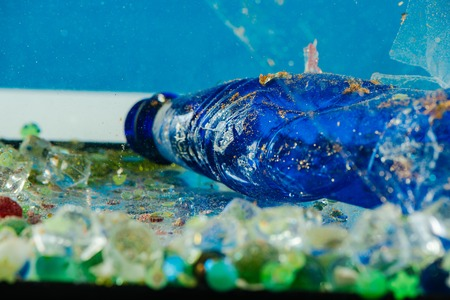 Transparent ruined plastic. Dirty blue crumpled bottle being covered with dust and rust and lying in trash