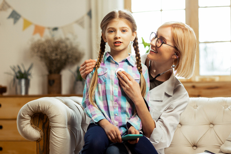 At the office of a doctor. Cute sick pretty girl with long brown braids sitting on the knees of pleasant smiling glowing pediatrician while she is examining lungs of a girl with a stethoscope.