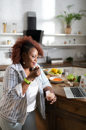 So interesting. Amazing curly haired woman standing at the table and looking at her computer