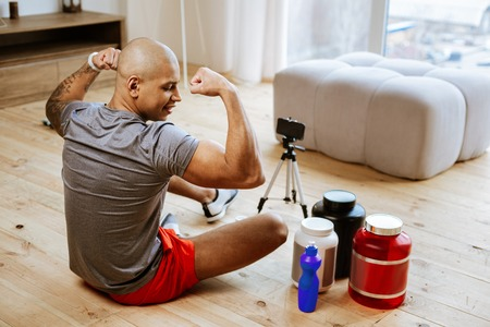 Phone stand. Bald bodybuilder showing his biceps while making photo using smartphone and phone stand Imagens