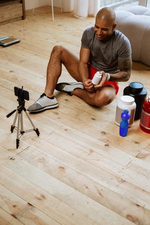 Blog on smartphone. Young bald sportsman filming blog on smartphone while sitting on the floor