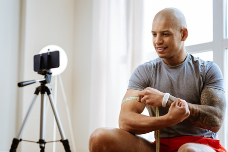 Body and biceps. Dark-skinned bodybuilder wearing white smart watch measuring biceps in front of camera