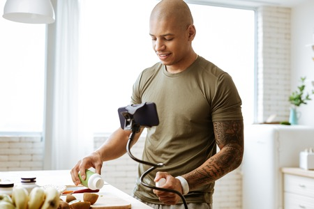 Taking vitamins. Dark-skinned bald young bodybuilder taking vitamins while cooking breakfast