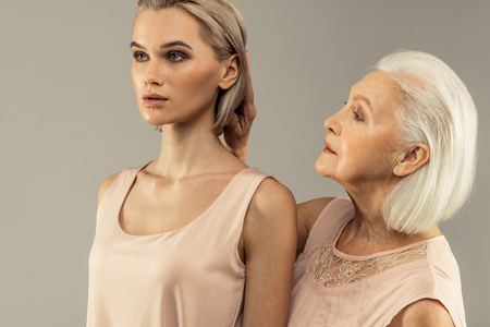 Amor de madre. Agradable mujer de edad tocando el cabello de sus hijas mientras está de pie detrás de ella