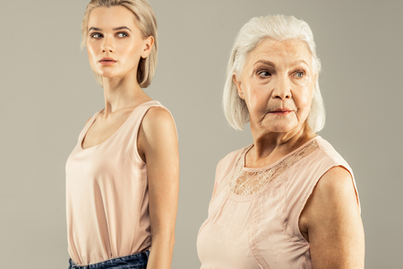 Older generation. Nice aged woman turning her head while standing in front of her daughter