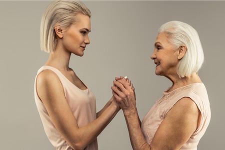 Besondere Verbindung. Angenehme nette Frauen, die sich gegenseitig die Hände halten, während sie sich gegenüberstehen