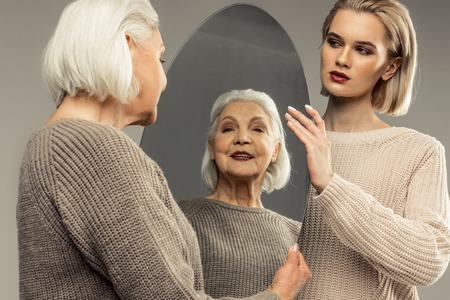 Great mood. Delighted aged woman looking into the mirror while smiling to herself