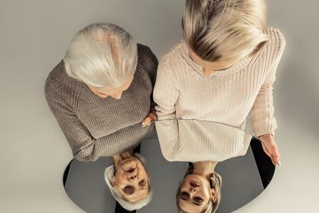 Spiegelreflectie van jonge en oude vrouwen terwijl ze samen staan Stockfoto