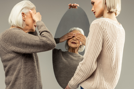 I do not want to see. Pleasant aged woman closing her eyes while standing in front of the mirror Imagens