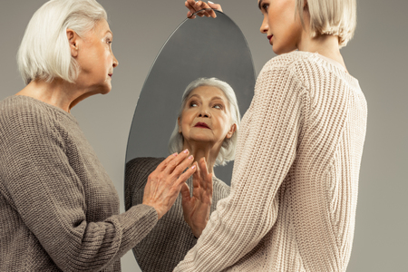 How do I look. Pleasant elderly woman looking at herself while standing in front of the mirror