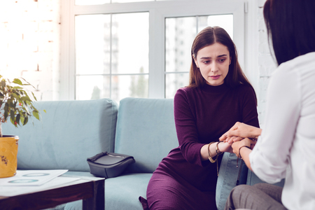Lady visiting psychologist. Crying depressed upset attractive young lady being comforted during a visit to a psychologist