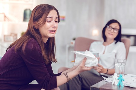 Being emotional. Crying upset attractive young brown-haired lady wearing knitted dress going emotional during physiological therapy with a counselor
