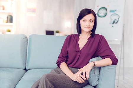 Woman in a living room. A beautiful dark-haired elegant woman wearing purple blouse sitting on a living room couch Stock Photo