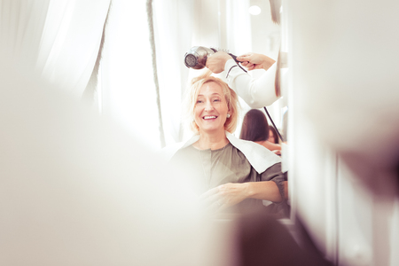 Amazing blonde female keeping smile on her face while looking at her reflection