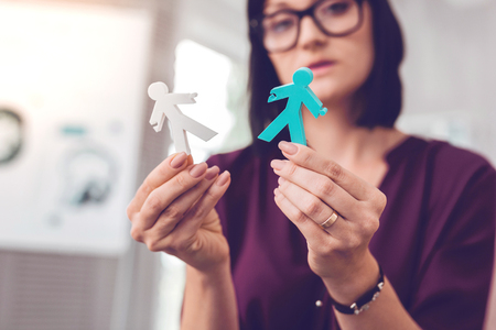 Keeping human figures in hands. Focused alluring stylish dark-haired manager wearing glasses keeping human stick figures in hands.
