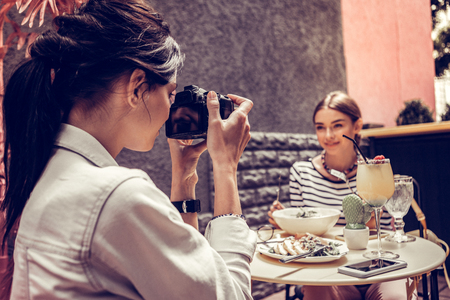 Beautiful pictures. Delighted nice woman taking a photo of her friend while sitting opposite her at the table