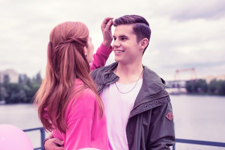 Lachende vriendin. Mooi langharig meisje corrigeert het kapsel van haar lachende vriendje terwijl ze knuffelt aan de kust van de rivier Stockfoto