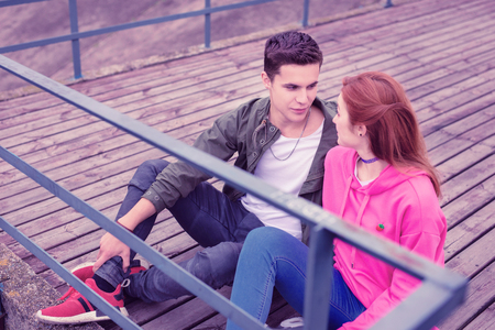 Happy with relationships. Young dark-haired guy lovely looking on her ginger girl while having date outside