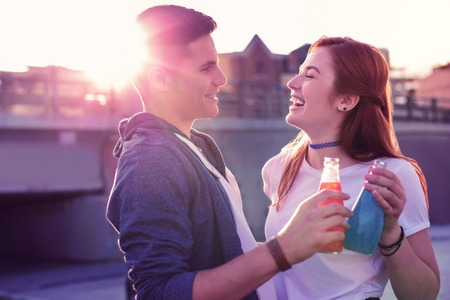 Sweet drinks. Laughing ginger girl in white t-shirt spending time with her handsome boyfriend while meeting lovely sunset
