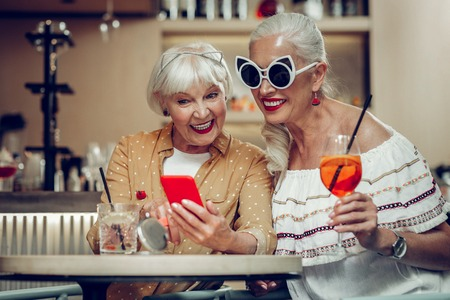 Nice aged woman sitting together with her friend while showing a picture on her phone