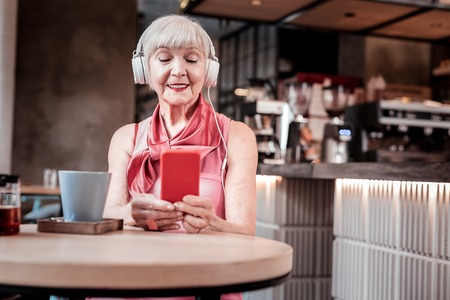 Bright makeup. Peaceful short-haired old woman enjoying favorite music while visiting cafe and wearing spacious headphones