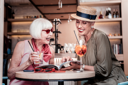 Fashionable senior lady. Laughing good-looking senior girlfriends sitting together in a cafe and flipping through magazine pages 写真素材