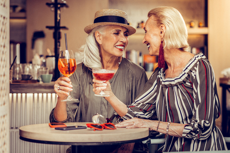 Celebrating reunion. Beautiful grey-haired elegant women resting in a bar with bright cocktails