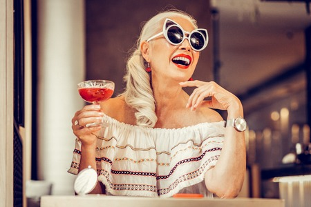 Glass of cocktail. Laughing long-haired senior woman wearing weird glasses and carrying red cocktail