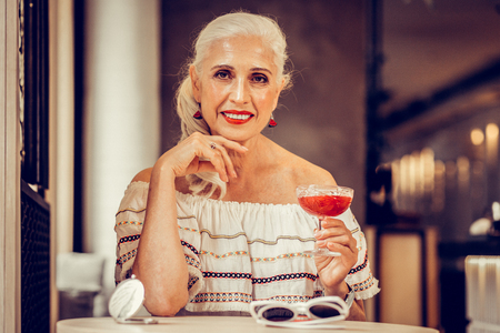 Carrying red cocktail. Smiling grey-haired woman with red lips wearing off-shoulder blouse while sitting in a bar