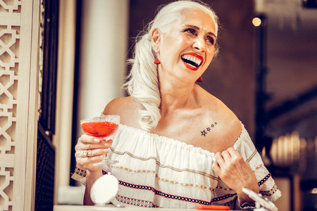 Wearing off-shoulder blouse. Laughing fashionable old woman showing tattoo underneath her blouse while visiting bar