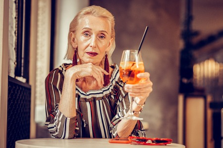 Refreshing drink. Thoughtful short-haired senior woman wearing bulky jewelry while leaning on the table in cafe