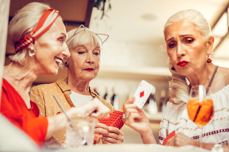 Making jokes. Upset long-haired old woman showing her cards during gambling game with cheerful girlfriends