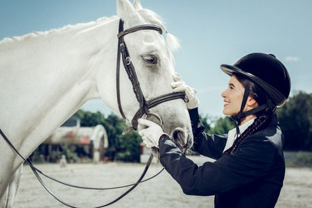 Beautiful mammal. Pleasant pretty woman smiling while looking at the white horse Stock Photo