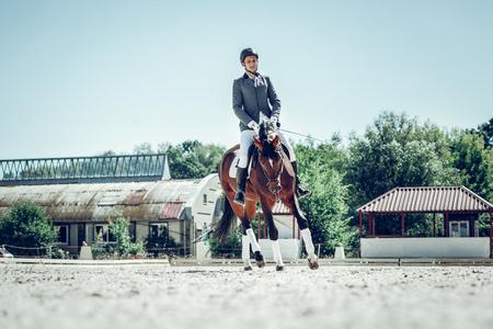 Mastering skills. Pleasant young rider mastering his riding skills while having his training Stock Photo