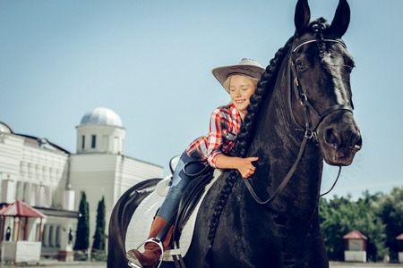Best friend. Positive cute girl smiling while hugging her horse