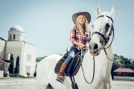 My hobby. Beautiful blonde girl sitting on a white horse while enjoying riding on it