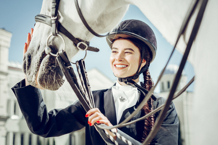 Feeling of happiness. Joyful pretty woman looking at her horse while stroking it with her hand Stock Photo