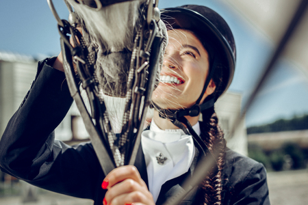 Absolute happiness. Cheerful nice woman looking at her horse while expressing her positive emotions