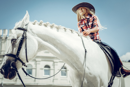 So interesting. Nice cute girl smiling while enjoying her riding lesson