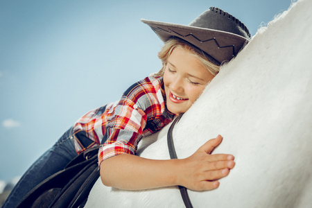 Absolute happiness. Delighted nice girl sitting on her horse while expressing her love to it