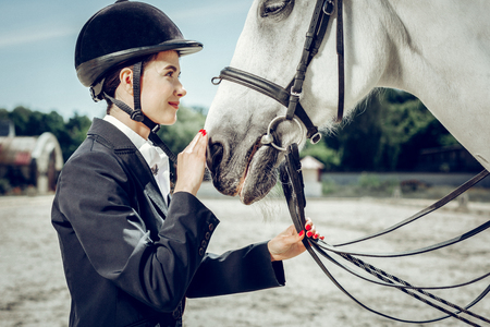 Special connection. Pleasant young woman looking at her horse while touching its nose