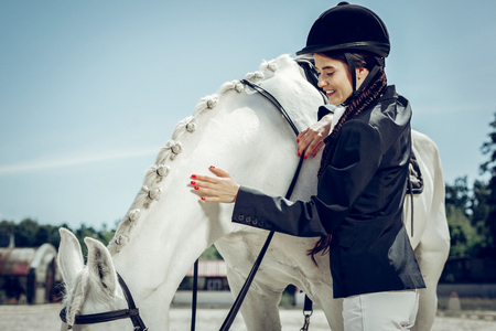 Love and care. Joyful positive woman smiling while expressing love and care to her horse