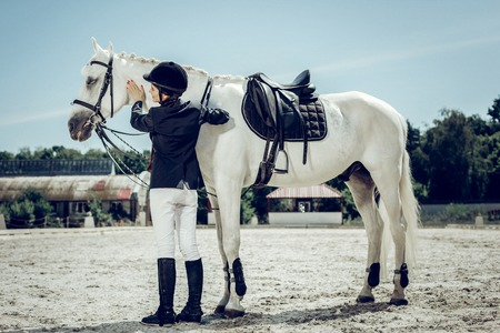 Professional female rider. Joyful nice woman standing near her horse while wanting to ride it